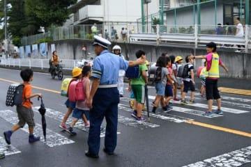 署員や女性白バイ隊員らが児童の登校を見守った=横浜市西区