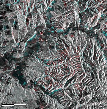 衛星だいち2号が地震前と地震後に撮影した画像を合成した、北海道厚真町吉野地区周辺。土砂崩壊が起きた森林を赤色で、崩れた土砂や樹木が積もっている部分を水色で示している(JAXA提供)