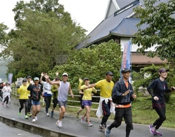金栗四三の走った通学路を体験するランニングイベントで金栗の生家前を走り抜ける参加者たち=和水町