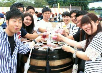 安心院産ブドウのオリジナルワインなどを楽しむ来場者=8日、宇佐市安心院町の家族旅行村「安心院」