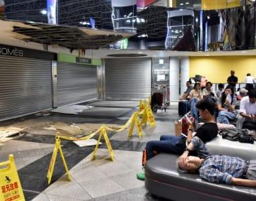 地震ではがれ落ちた天井板。空港ロビーには飛行機を待ち、疲労を色濃くする旅行者らであふれた=7日午後6時55分、北海道千歳市・新千歳空港
