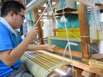 ジャカード織機を使う利用者。工房には3台の機械が入り、さまざまな製品を織る(京都市北区大将軍川端町・西陣工房)