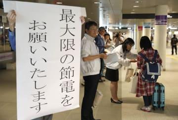札幌市の地下歩道に立ち、節電を呼び掛ける北海道電力の社員ら=9日午後