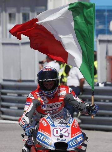 世界選手権シリーズ第13戦、サンマリノGPを制し、地元イタリアの国旗を掲げるドゥカティのアンドレア・ドビツィオーゾ=9日、ミサーノアドリアティコ(AP=共同)