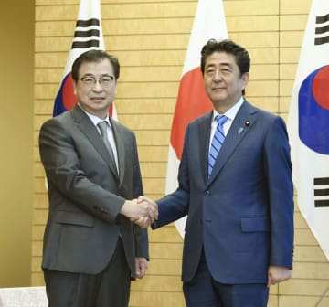 面会前、韓国特使団メンバーの徐薫国家情報院長(左)と握手する安倍首相=10日午前、首相官邸