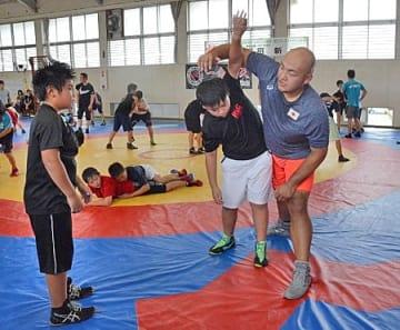 子どもたちにレスリングを教える園田選手(右)=滋賀県日野町上野田・日野高