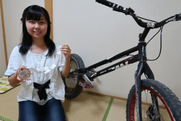 バイクトライアルの世界大会で3位に入賞し、銅メダルを掲げる平野さん(京都市伏見区の自宅)