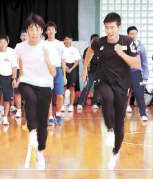 中学生と走りながらフォームなどを教える桐生選手(右)