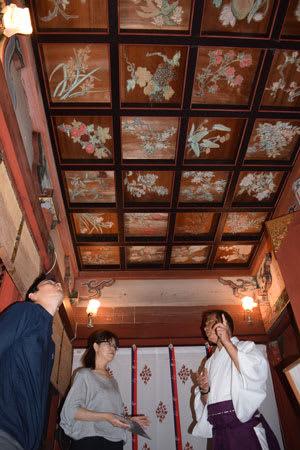 佐々木宮司から説明を聞き、花の天井を見上げる参拝者(京都市右京区・平岡八幡宮)