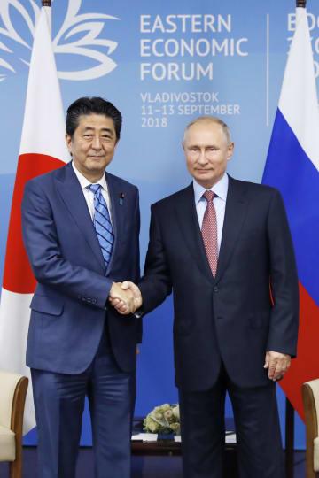 会談前、握手する安倍首相(左)とロシアのプーチン大統領=10日、ウラジオストク(共同)