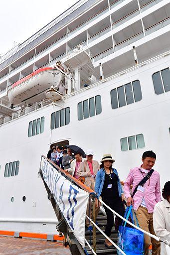 青森港に帰港した「飛鳥II」から下りる乗客=10日午後、新中央埠頭