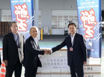 中国山東省の自治体幹部(右)を招き、九州経済連合会が開いた養殖ブリの出荷式典=11日午前、福岡空港