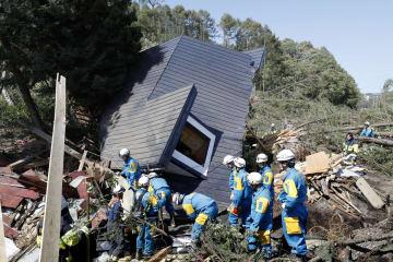 6日、大規模な土砂崩れで建物が倒壊した現場で捜索する警察官ら=北海道厚真町
