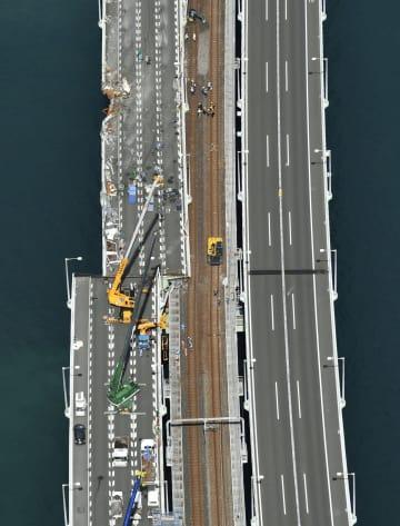 台風21号の影響によるタンカー衝突で道路部分が鉄道線路側にずれた関西空港の連絡橋=11日午前10時17分(共同通信社ヘリから)