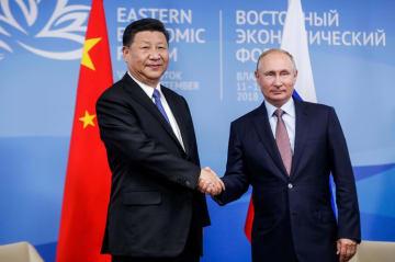 11日、ロシア・ウラジオストクでの首脳会談で握手するプーチン大統領(右)と中国の習近平国家主席(タス=共同)