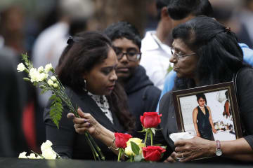 米中枢同時テロから17年を迎えた11日、ニューヨークの世界貿易センタービル跡地付近で開かれた追悼式典で花を手向ける女性(AP=共同)