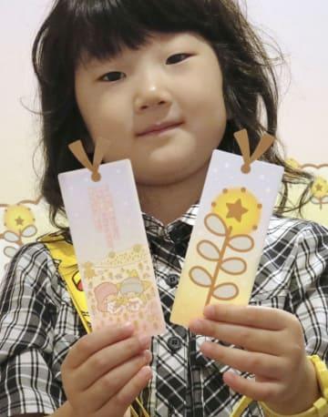 キキとララがインターネット上で育てた「希望の花」のしおりを手にはにかむ熊谷愛海ちゃん=8日、宮城県石巻市の石ノ森萬画館
