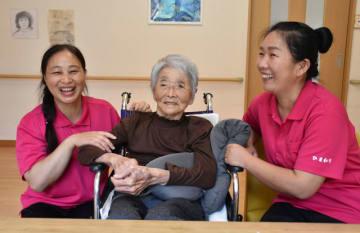 介護施設入所者とふれあう簡さん(左)と柴さん(右)