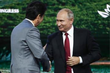 東方経済フォーラムで安倍首相(左)と握手するロシアのプーチン大統領=12日、ウラジオストク(タス=共同)
