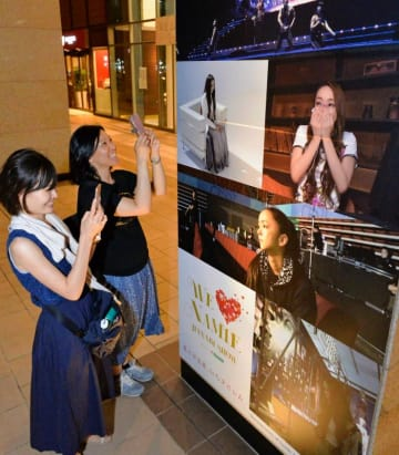 タイムスビルの柱に張られたポスターを写真に収めるファン=那覇市久茂地