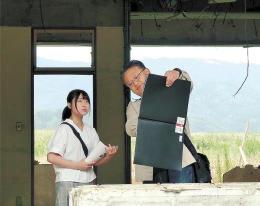 曽祖父ゆかりの旧大川小で、只野さんの説明を聞く三島さん(左)