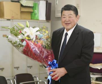 記者会見を終え、花束を手にする元小結大錦の山科親方=13日、両国国技館
