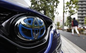 販売店に並べられた車両に付けられているトヨタ自動車のロゴマーク=東京都港区