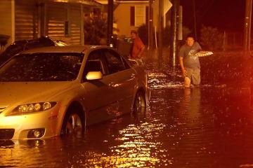 13日、米ノースカロライナ州で、道に水があふれ避難する男性ら(ゲッティ=共同)