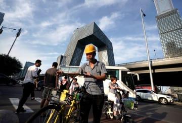 自転車を引いて中国中央テレビ局(CCTV)の前を歩く建設労働者=8月、北京(ロイター=共同)