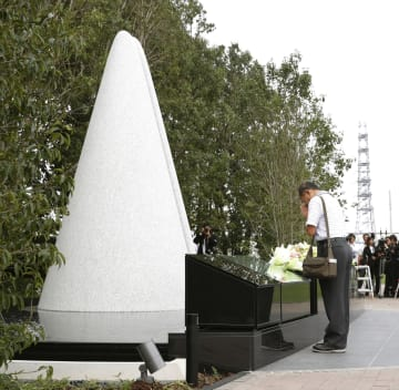 整備工事が完了した尼崎JR脱線事故の現場マンション前で、慰霊碑に手を合わせる遺族の上田弘志さん=14日午後、兵庫県尼崎市