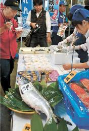 はらこ飯を試食する市場関係者=14日午前5時40分、仙台市若林区の市中央卸売市場