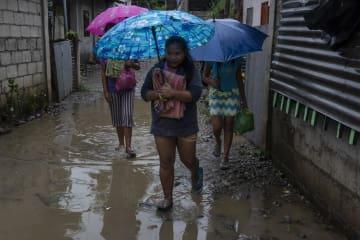 14日、フィリピン・ルソン島北東部トゥゲガラオで台風22号に備え避難する人たち(ゲッティ=共同)
