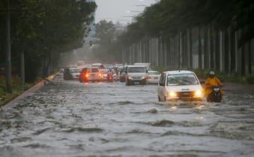 15日、台風の影響で水に漬かったマニラの道路(AP=共同)