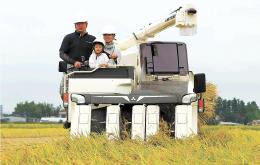コンバインに乗り込み、収穫を体験した親子ら