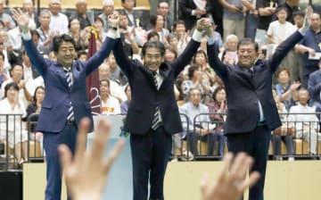 津市で開かれた自民党総裁選の演説会で、聴衆に手を振る安倍首相(左)と石破元幹事長(右)ら=16日午後