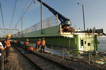 関西空港連絡橋の鉄道部分の復旧工事現場。奥は橋桁の一部が撤去された自動車専用道路=16日午後