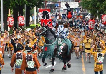 勢子らの掛け声とともに、勇壮に繰り広げられた「馬追い」=16日午前、熊本市中央区の日銀熊本支店前(高見伸)