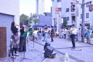 路上ライブの音楽を聴く人たち