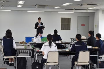 試験の進め方について、みちのく銀行の人事担当者から説明を聞く高校生たち=16日、青森市のアスパム