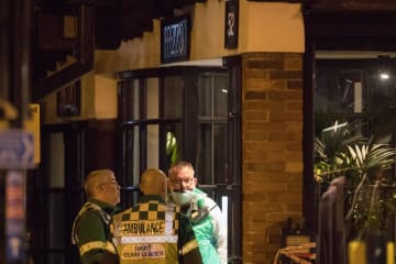 16日、英南部ソールズベリーで、2人が不調を訴えたレストランの周辺に集まる警察当局者ら(ゲッティ=共同)