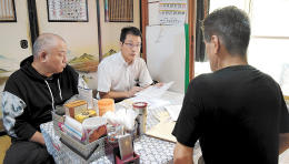 今もトイレと風呂が使えない家屋に暮らす男性(右)。貧困や健康問題などについて中尾弁護士(中央)と伊藤代表理事が聞き取りをした