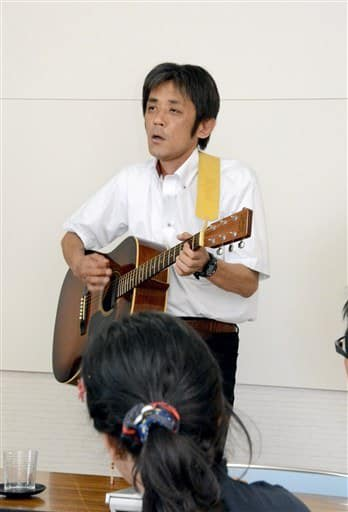 就労移行支援事業所「オルタナ」での講演で、自作の歌を披露する中村敏さん=熊本市北区