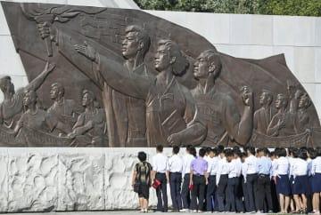 祖国統一三大憲章記念塔を訪れた学生ら=17日(共同)