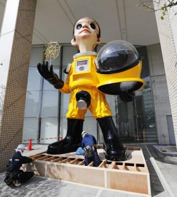 撤去作業が始まった、防護服姿の子どもの立像「サン・チャイルド」=18日午前、福島市