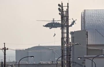 米軍嘉手納基地内でホバリングする海軍のHH60Hヘリから降下訓練する米兵=18日午後4時40分(読者提供)
