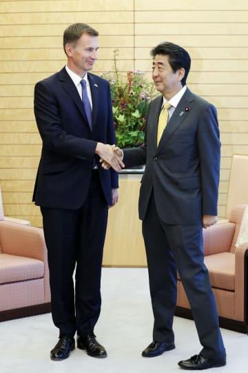 会談前、英国のハント外相(左)と握手する安倍首相=18日、首相官邸