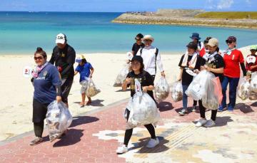 「WE ♥ NAMIE HANABI SHOW」の会場のごみを拾ったボランティアたち=宜野湾市・トロピカルビーチ