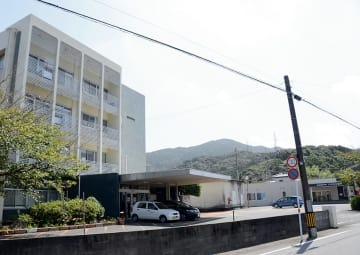 本年度末で廃止予定の八代市立病院。熊本地震後は右奥の仮設棟で外来診療を続けている=同市