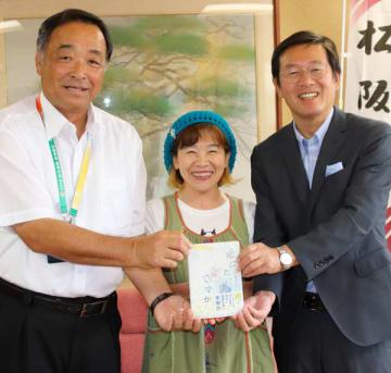 【竹上市長(右)に新作「死にたい、ですか」を贈った村上さん(中央)=松阪市役所で】