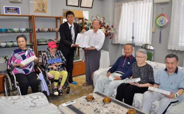 【岡山会長(中央)らにたばこを手渡す西川支店長(左から3人目)=津市高洲町の青松園で】